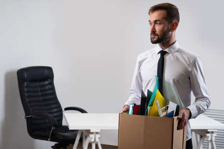 Man lost his job. Guy with a cardboard box in his hands. Box as a symbol of dismissal. Upset man looks away. Concept is job loss. Guy lost his job due to the crisis. Young human is dissmised.