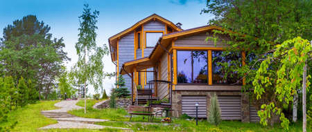 Vacation home. Cottage is in a picturesque location. Concept - Purchase of Real Estate elite. Wooden house on a summer day. Concept - landscape design services. Architecture. Landscaped country house