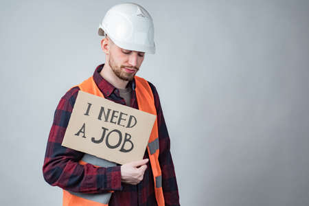 I need a job.Builder is looking for work. Concept - dismissal workers building. Sad guy with a sign in his hands. Inscription need a job on cardboard. Concept - layoffs due to closure of construction 版權商用圖片