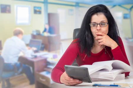 Displeased accountant is looking at calculator. Concept - accountant distressed by financial situation. Lot of documents in front of a woman. Girl in large office. Concept - company ran out of money Imagens