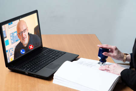 Video interview. Accountant talking to a man through videoconference. Concept - consulting. Man puts a stamp. Concept - Recruiter makes decision online. Providing consulting services remotely. Laptop