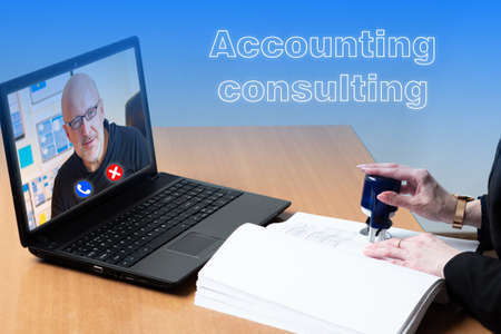 Accounting consulting. Concept - accountant consults remotely. Video communication works on a laptop. Consultant is running remotely. Hand puts a stamp in documents. Provision of remote services.