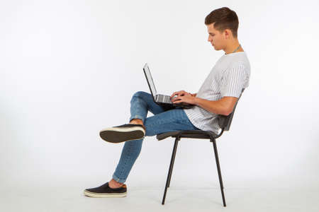 A man is sitting on a chair with a laptop. A young man with a laptop sideways to the camera. Computer gadgets. Communication via the Internet. A young man with a laptop on a white background. 免版税图像