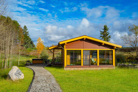One-story cottage with a beautiful sky background. Private house on the autumn landscape. Panoramic glazing of the cottage verandah. Hot tub next to the country house. House on the lawn and a walkway.