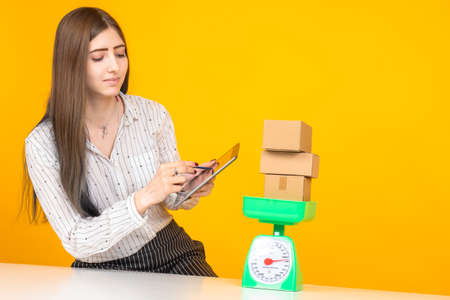 Weighing. Concept - checking the weight of the goods received. Girl measures the weight of the parcel. Boxes on the scales. A woman writes weight to a tablet. Female student on an orange background