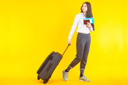 Girl was going on a trip. Traveler is looking at the ass. Woman with travel suitcases. Student with documents and travel bag. Girl on a yellow background. Concept - woman at the airport