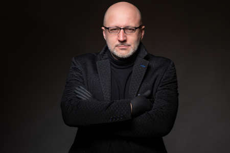 Adult human on a dark background. A man with glasses is looking at the camera. Portrait. Bald man in dark clothes. Concept - human in mourning clothes. Adult man in dark overcoat