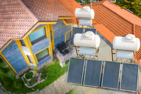 Solar panels near the house. Concept - installation of solar cells. Boilers for heating water. Sale of power generating equipment. Concept - green energy. Solar water heater.