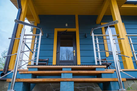 Staircase leads to entrance to house. Steps to cottage door. House is tiled with multi-colored wood. Ragment of a country cottage. Concept - sale of facing materials. Facing a country cottage.