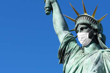 Statue of Liberty in a medical mask. Concept - pandemic in the USA,. Statue of Liberty on the background of blue sky. Concept - quarantine in New York. Place for an inscription. Epidemic in America. Reklamní fotografie