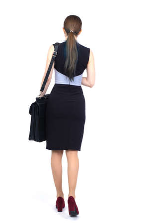 Woman dressed in business style back view. Businesswoman in full growth from back. Woman in a business skirt on a white background. Concept - she goes somewhere. Businesswoman with a briefcase.