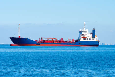 Tanker on the ocean backdrop. Chemical tanker is sailing on sea. Ship for transportation of chemical products. City can be seen in the distance. Chemical tanker is painted blue and red.