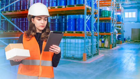Warehouse of chemical products. Woman works in a warehouse of chemical plant. Girl in helmet and orange vest. Concept - a girl is looking for something in warehouse. Large barrels are stored on racks