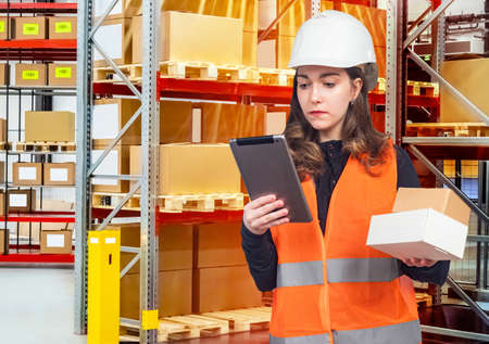 Girl works a warehouse worker. Concept - woman working with blue collar. Young woman on background of storage racks. Woman with tablet is standing in warehouse. Concept - inventory. Girl holds boxes