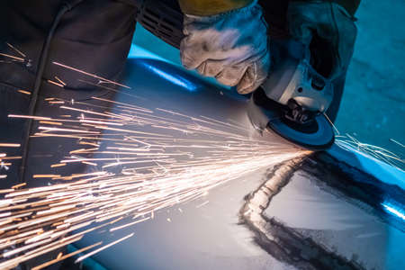 Man polishes metal. Master works with a grinding machine. Leveling material. Concept - alignment of car body. Body work in a car workshop. Sparks fly from under grinding machine. Angle grinder