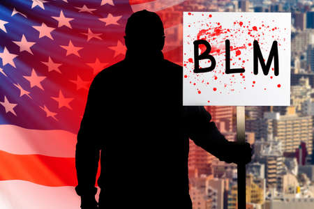 African American protests in the USA. Protest against killing of blacks. Man with a bloody banner. Man on background of USA flag. Riots in America. Inscription BLM on banner. Riots in Michegan. Blood