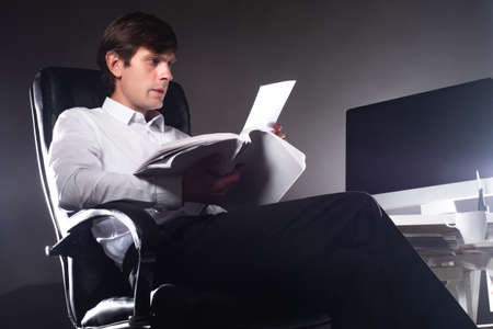 Overtime. Office worker works night. Guy reads documents while sitting in a dark room. Man in his own room works late. Office worker is working overtime. Works while sitting in dark. Overtime work. Imagens