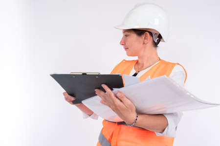 Woman engineer. Engineer with many papers in his hands. Woman in an orange canopy and a protective helmet. Clipboard and paper in hands of a woman builder. Concept - career of engineer or builder