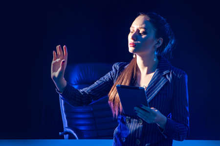 Businesswoman next to a work desk. Businesswoman waves her hand to someone. Woman with a tablet in her office. Stockfoto