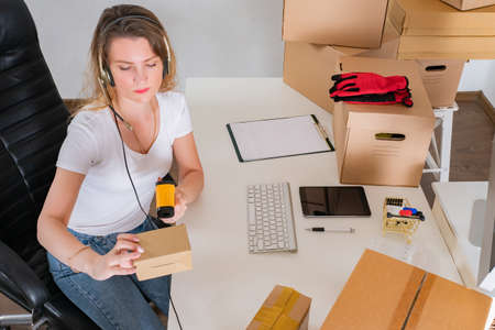 Woman owner shop. Woman scans barcode on parcel. Data collection terminal is in hands of owner shop. Lot of boxes on business woman desktop.