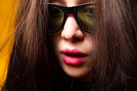 Surprised girl in sunglasses. Close-up of a woman face in sunglasses. Brunette girl is very surprised. Portrait of a brunette in sun glasses. Sunglasses woman fashion.