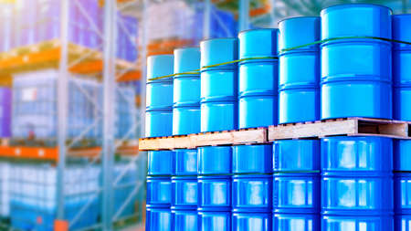 Blue barrels are stored in several levels. Concept - oil storage containers. Metal barrels as a symbol of oil production. Barrels in the warehouse of an oil refinery. Crude petroleum in stock.