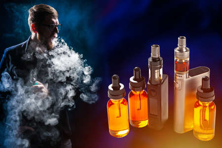 Vaping. Vaper crit and looks at vape devices. A man smokes steam in the dark. A young man in clouds of smoke. Oils for vape. Concept - sale of Veping liquids. Juices for a vape device. Imagens