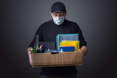Sad man with a box in his hands. Layoffs from work. Concept - sick person came under reduction. Concept - guy was fired due to fever. Man was forcibly sent quarantine. Cardboard box with stationery.