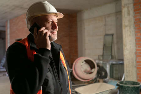 Builder is talking on phone. Worker inside building under construction. Concept - builder calls architect. Renovated premises in background. Builder worker in white hard hat. Workplace repairman.