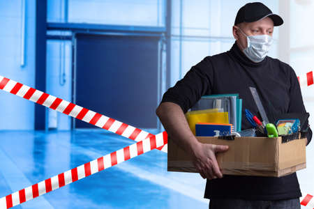 Man fired due quarantine. Concept - the introduction of quarantine led to dismissal. Man in a medical mask holds box. Concept - enterprise is cutting staff. Human carries box with personal belongings