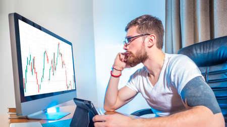 Financial analyst. Concept - a man works as a stock broker. Trader in his own office. Guy is looking at the graphics on the monitor. Young man near the computer. Concept - young investor.