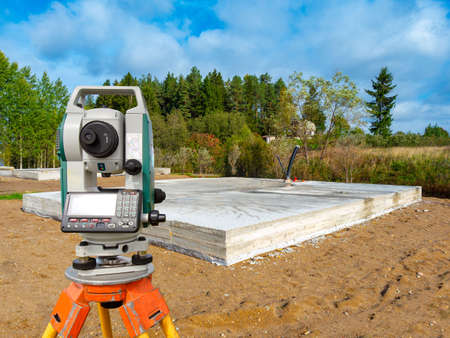 Geodetic works. Foundation of the future at home. Total station is mounted on a tripod. Concept - development of a tapographic plan. Total station next to the foundation. Cadastral work.
