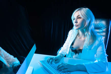 Successful business woman. Successful woman in workplace. Girl in a white suit on a dark background. Portrait of a successful businesswoman during work. Woman is typing something next to computer.
