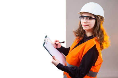 Woman in working uniform holds a clipboard. Orange vest as a symbol of inspection inspection. Woman inspector is writing something down. Girl in hard hat looks at camera. Place for inscription. Stock Photo