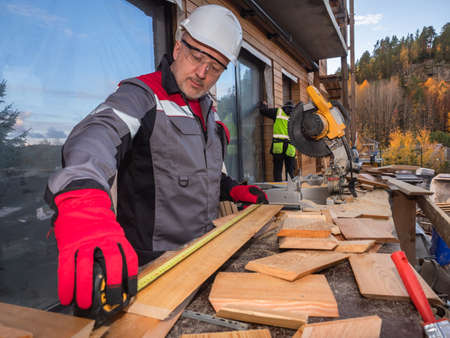 Joiner on a construction site. A carpenter measures a Board for covering of a private home. Woodworking in construction. Cottage with wood trim. Construction of a private house.