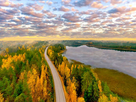 Autumn landscape from a height. A road under a beautiful sky. The highway runs along the river. The deserted road goes over the horizon. The concept of travel.