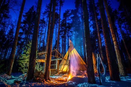 Winter teepee. Tipi in the woods at night. The lighted tent is surrounded by pine trees. Teepee against a beautiful sky. Ethnic housing in the winter forest.