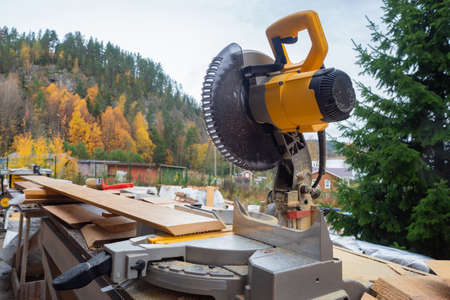Circular saw on an open-air construction site. Equipment for boards cutting on the background of the autumn landscape. Circular saw on a mountain background. Private house construction near the hill.