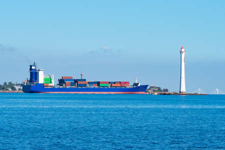 Sea cargo ship next to lighthouse. Sea container ship in distance. Vessel for transport of containers on shore. Concept - transportation of goods using sea container ship. Transportation by sea.