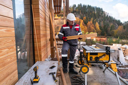 Man builds a cottage on the background of a beautiful mountain. Carpenter on the country house construction. Sawing machine next to the house under construction. Man is cutting boards on a machine. 版權商用圖片