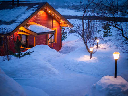 Christmas in the village. Cottage with garlands on the background of snow. Winter evening away from the city. A path in the snow leads to the house with garlands. The concept of home comfort.
