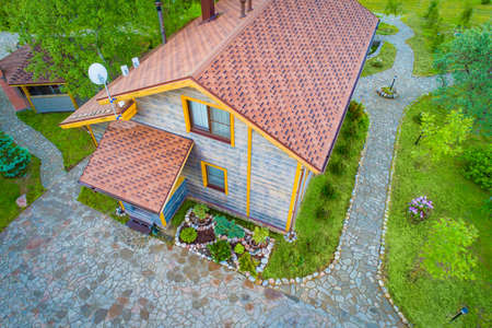 Two-story house view from a drone. Territory of the cottage is a top view. Landscaping near the house. Paths of the cottage are decorated with stone. Landscaping. Architectural design.