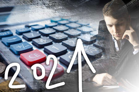 2021 year. Concept - expectation of financial return next year. Up arrow symbolizes profit. Man in a suit next to a calculator. Concept - guy makes a plan for 2021. Crisis recovery plans. Stock Photo