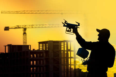 Man launches a quadcopter. Human with a drone in his hands next a construction site. Concept - construction observation with a drone. Control a erection of buildings with a drone. Construction cranes