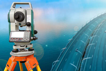 Total station near the bridge. Automobile bridge top view. Concept - construction of bridges. Concept - sale of a geodetic instrument. Total station as a symbol of tapographic work. Cartography