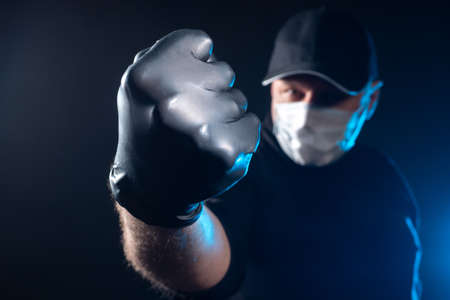 Man in a medical mask. Patient is in a pose of boxer. Man in protective mask and gloves. Concept - protection against viral infection. Countering virus. Concept - man fights against disease