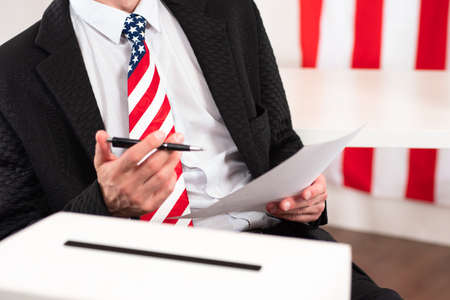 Presidential election USA. US. Voter polls during presidential election in USA. Presidential election using paper ballots. Man with pen and bill. Tie on voter in colors of American flag. Voting box.