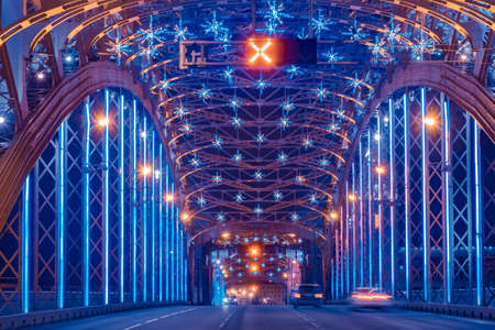 Bolsheokhtinsky bridge in Saint Petersburg. Road architecture of Russia. Christmas illumination inside bridge. Cars are driving across New Year Saint Petersburg.