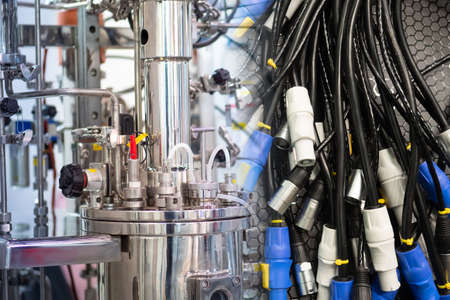 Bioreactor next to a variety of electrical cables. Electrical cords for connecting bioreactor. Electrical equipment. Concept - store of equipment for biological laboratory. Wires come from a reactor