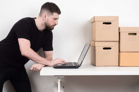 Mail worker is working with laptop. Man works next parcels. Guy registers mail. Young man is working with a computer while standing. Concept - guy works as a mail courier. Postman career. Carton box